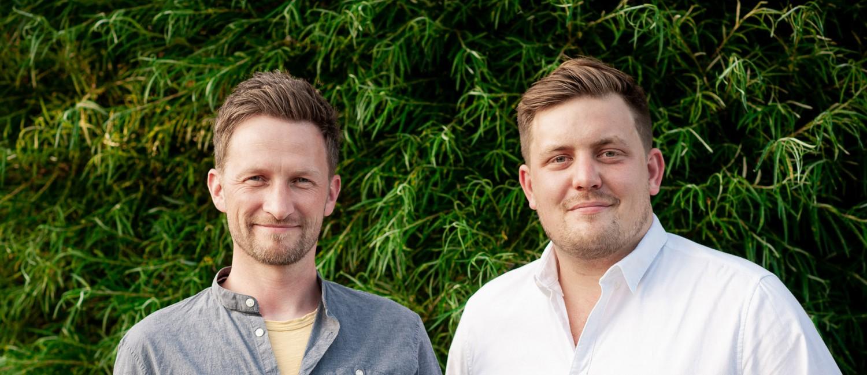 Sascha Baum-Stolberg und Kevin Weimann. Die Geschäftsführer von Kinderspielkunst vor einem natürlich, grünen Hintergrund.