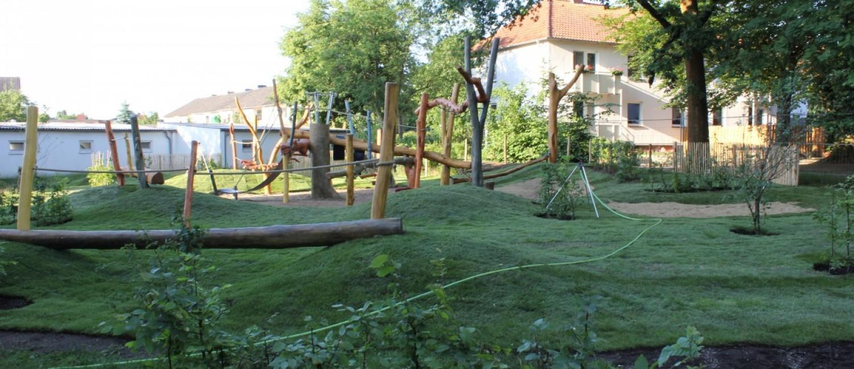 Spielplatz mit Spielgeräten für draußen in einer hügeligen grünen Parkanlage.